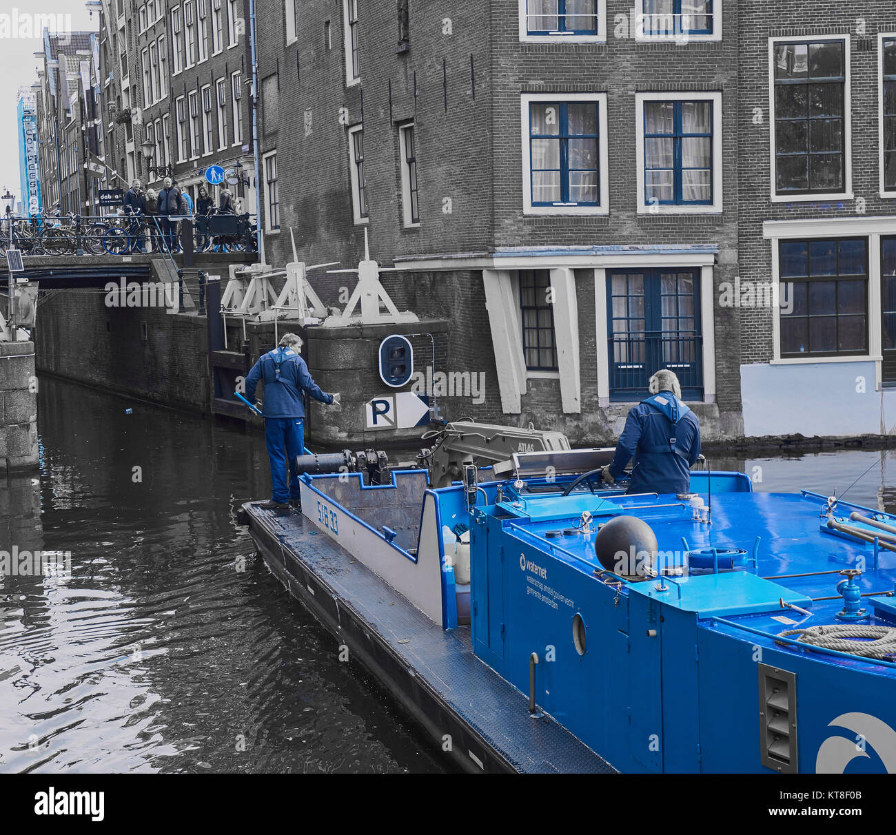 Man standing on cleaning barge fishing litter out of canal, Amsterdam, Holland - Stock Image