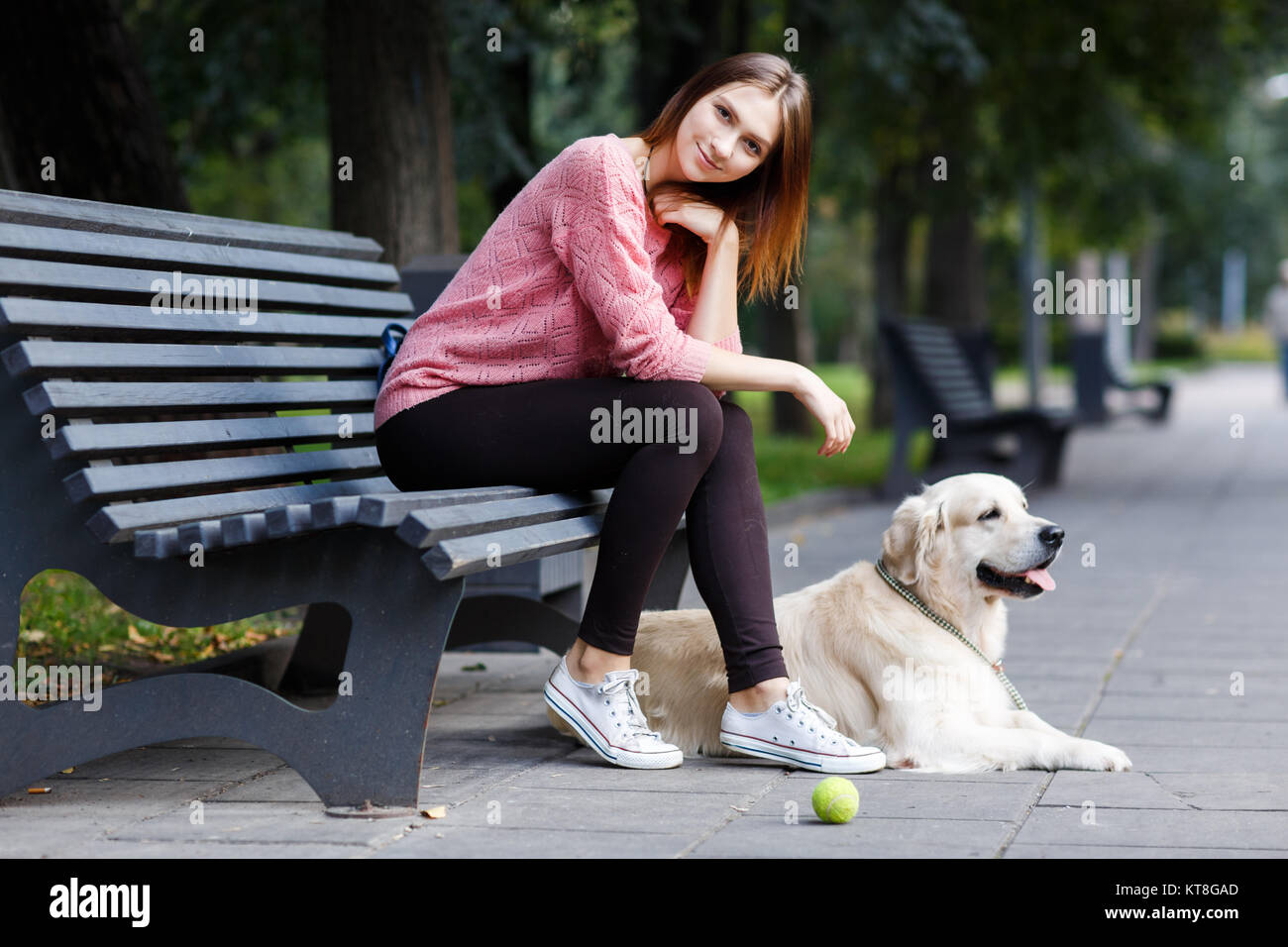 Picture of smiling woman sitting on bench, dog retriever on summer morning Stock Photo