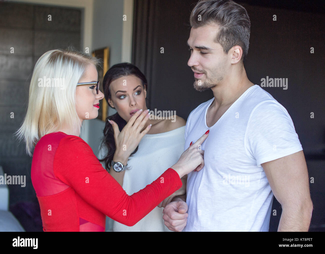 Blonde woman flirting with disloyal man, girlfriend in shock, indoors - Stock Image