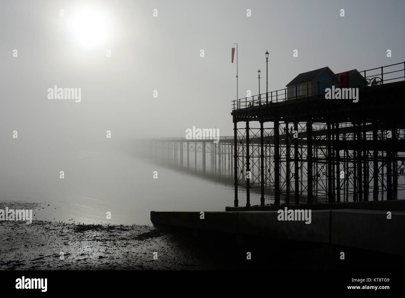 Thick fog hangs over the Thames Estuary, enveloping Southend Pier. People still walked it and used the train - Stock Image