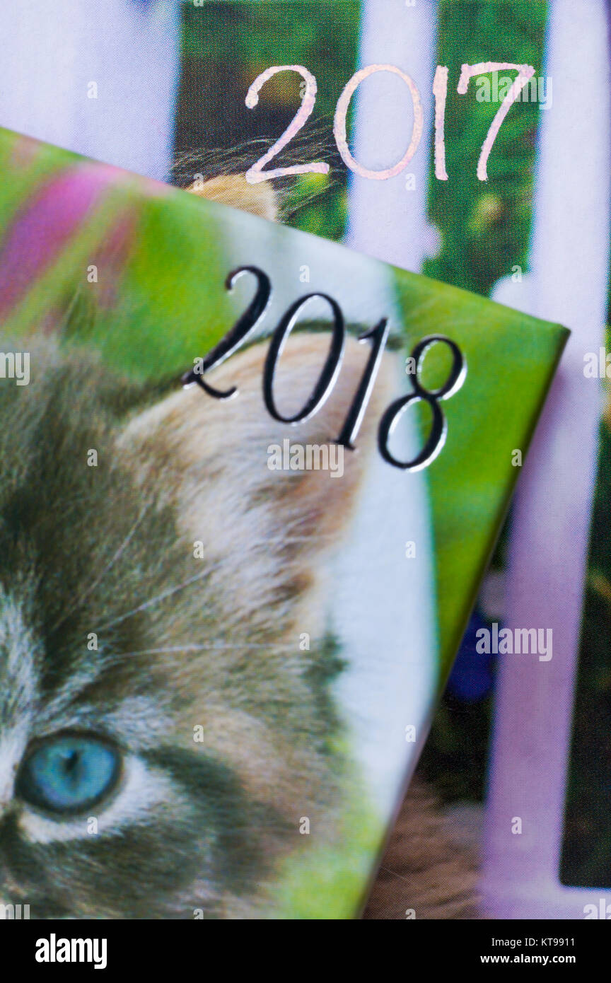 years showing on 2018 and 2017 diaries with 2018 in front and 2017 behind - concept moving into 2018 and leaving - Stock Image