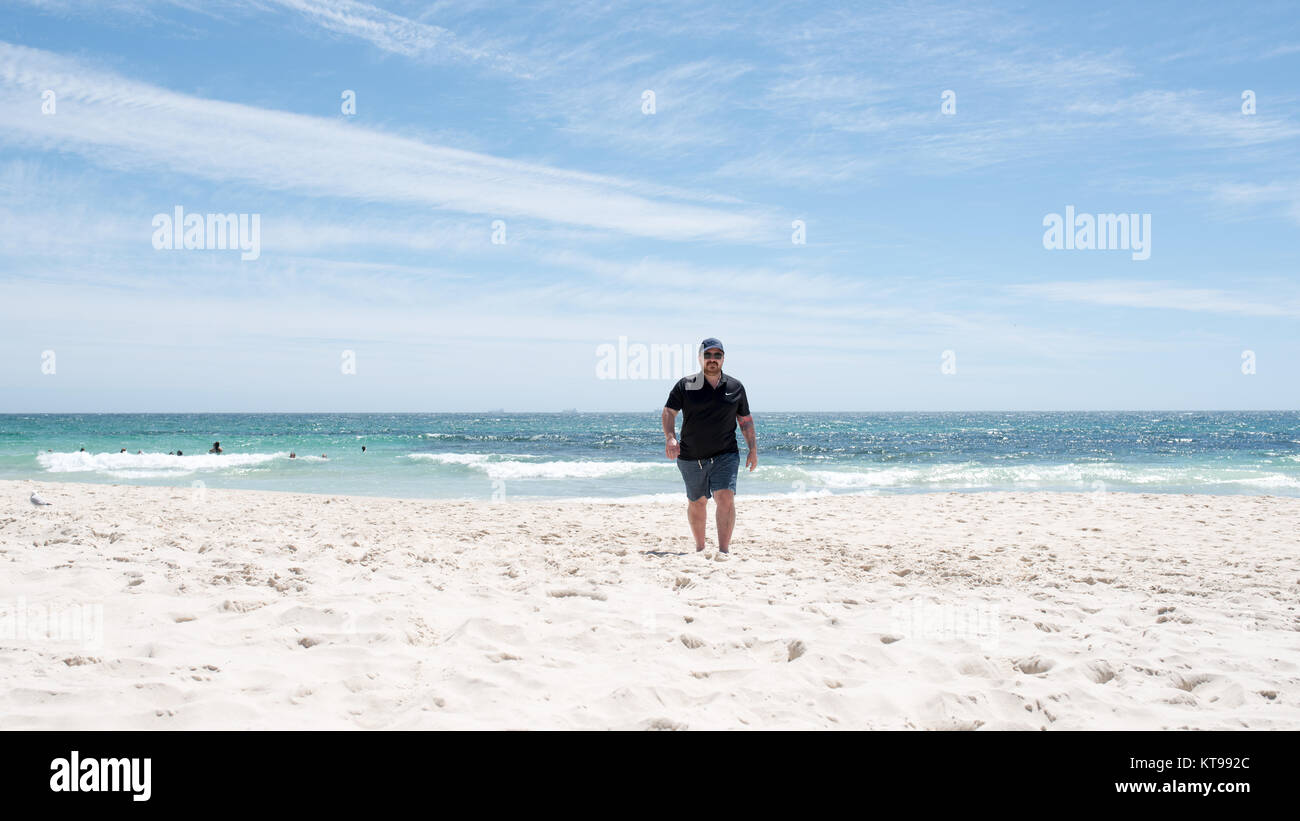 PERTH, Australia, WA / Western Australia - 2017 December 22, , Cottesloe . A man walks at the Cottesloe Beach . - Stock Image