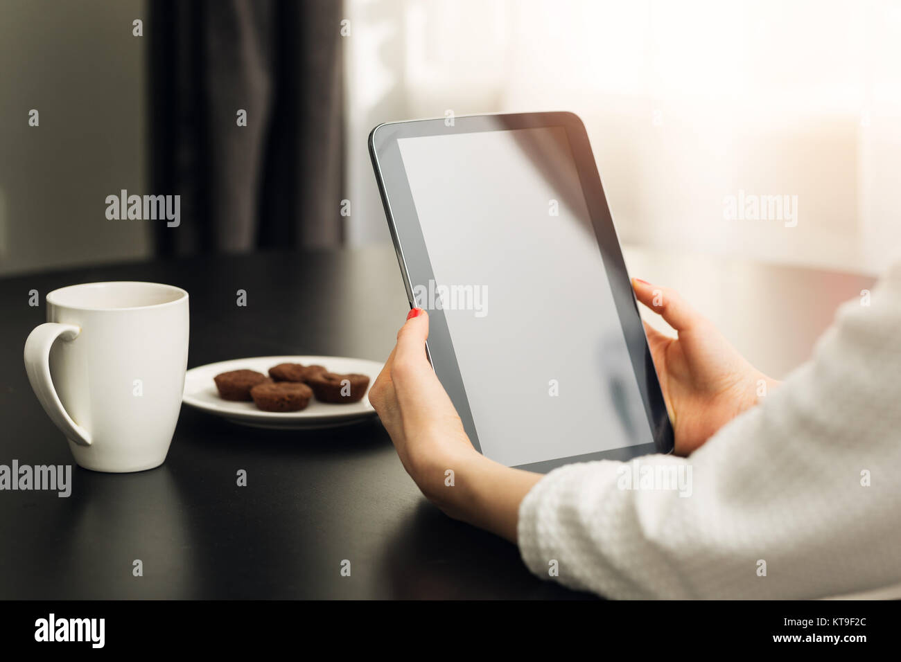 woman sitting by the the table at home and using digital e-book reader - Stock Image