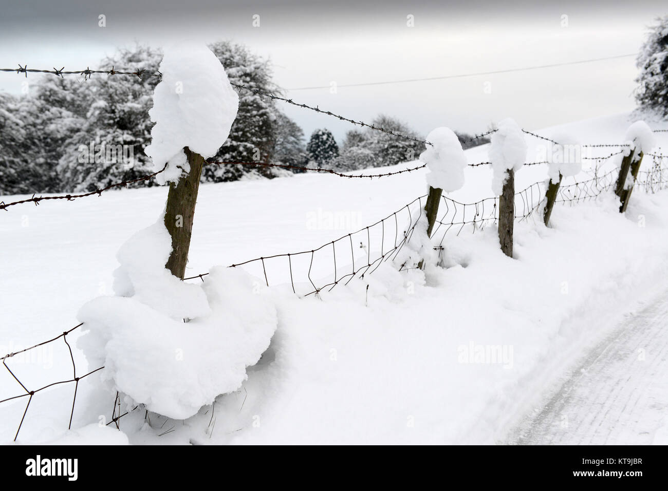 Deep snow on barbed wire fence winter 2017 - Stock Image