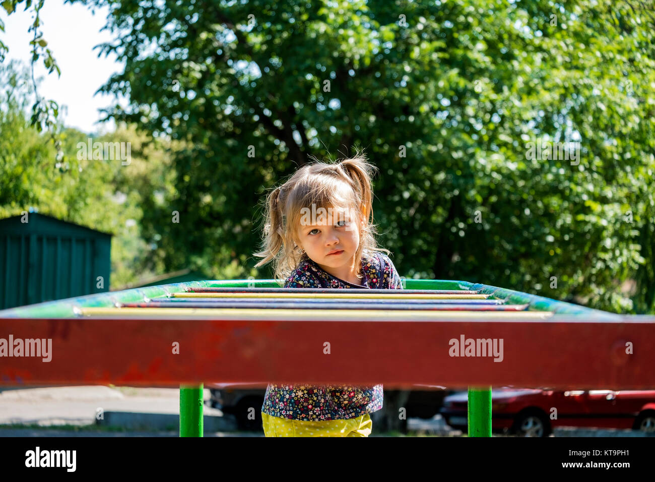 Little girl in yellow sherds and a floral tunic climbed through the staircase and bit her lip - Stock Image