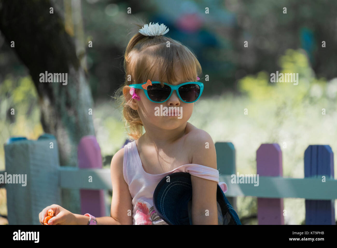 A small fashionista in the glasses with her bare shoulder looking into the distance - Stock Image