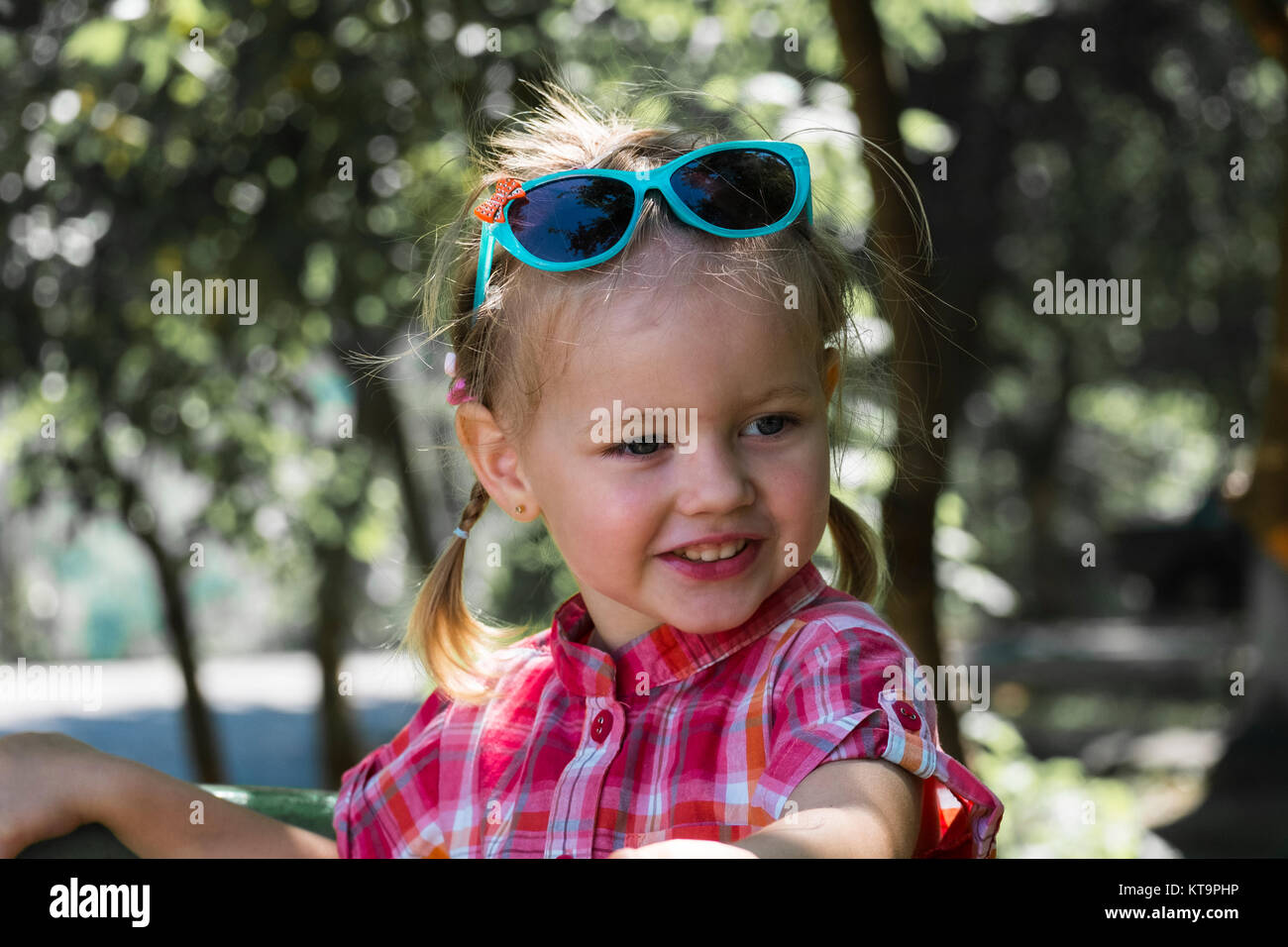 0151a6428 Happy little girl with a funny smile and turquoise sunglasses on her head -  Stock Image