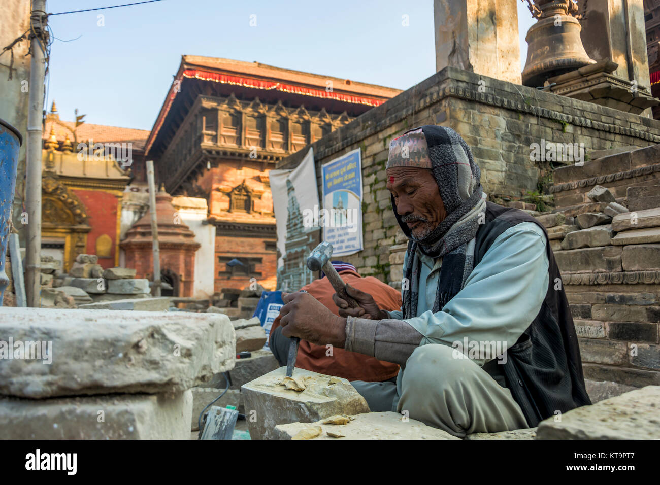 7 December 2017: Artist crafting stones at Bhaktapur Durbar Square renovate the temples damaged after the massive - Stock Image
