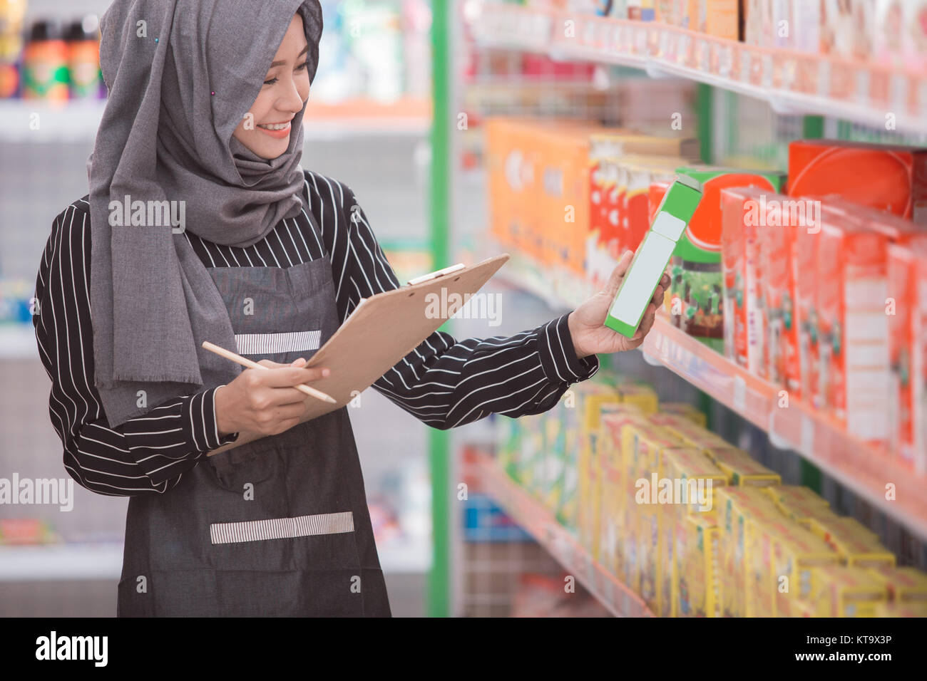 asian female muslim shopkeeper check the product at supermarket - Stock Image