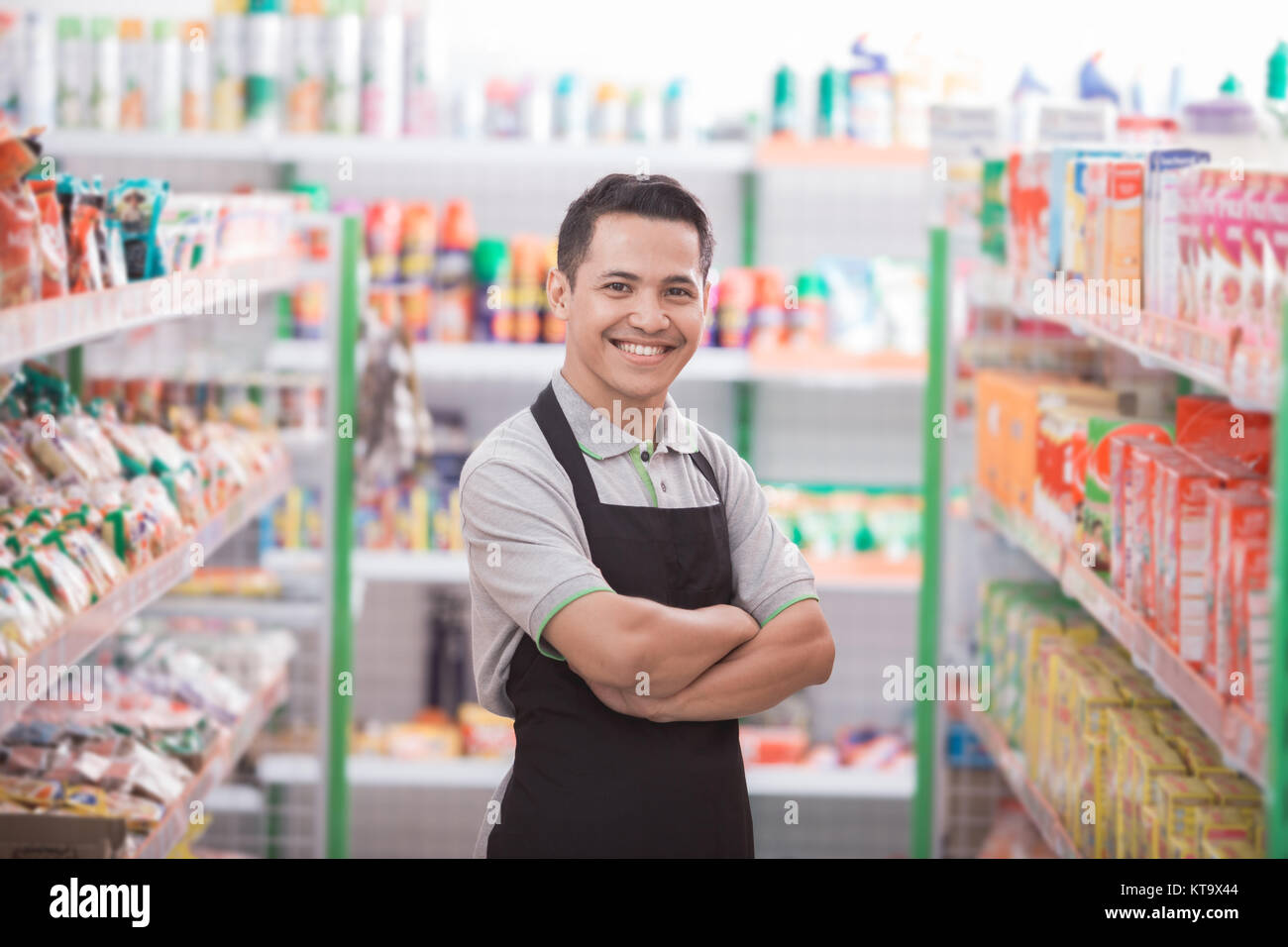 asian male shopkeeper standing in front of the groceries store - Stock Image