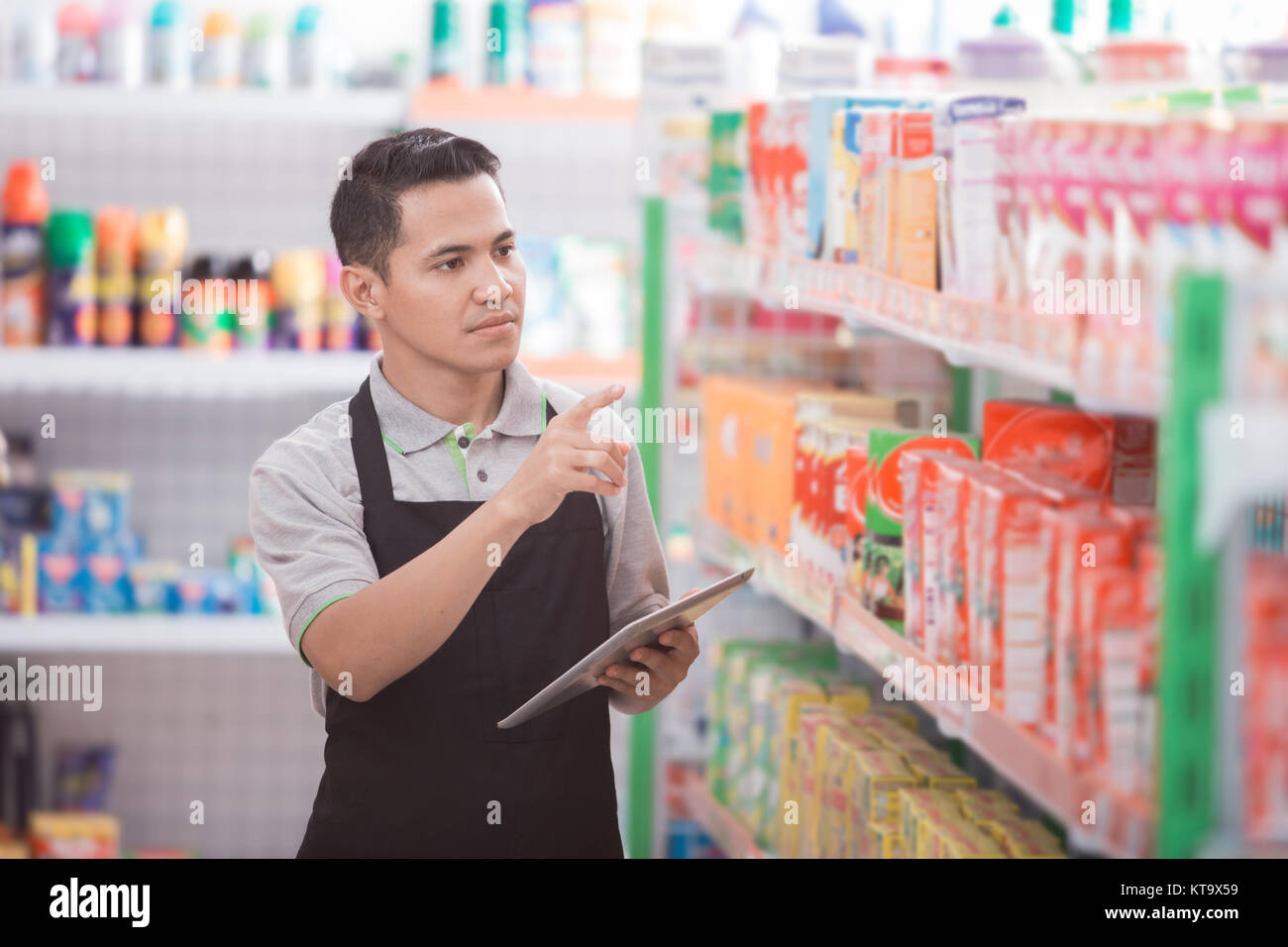 asian male shopkeeper working in a grocery store - Stock Image