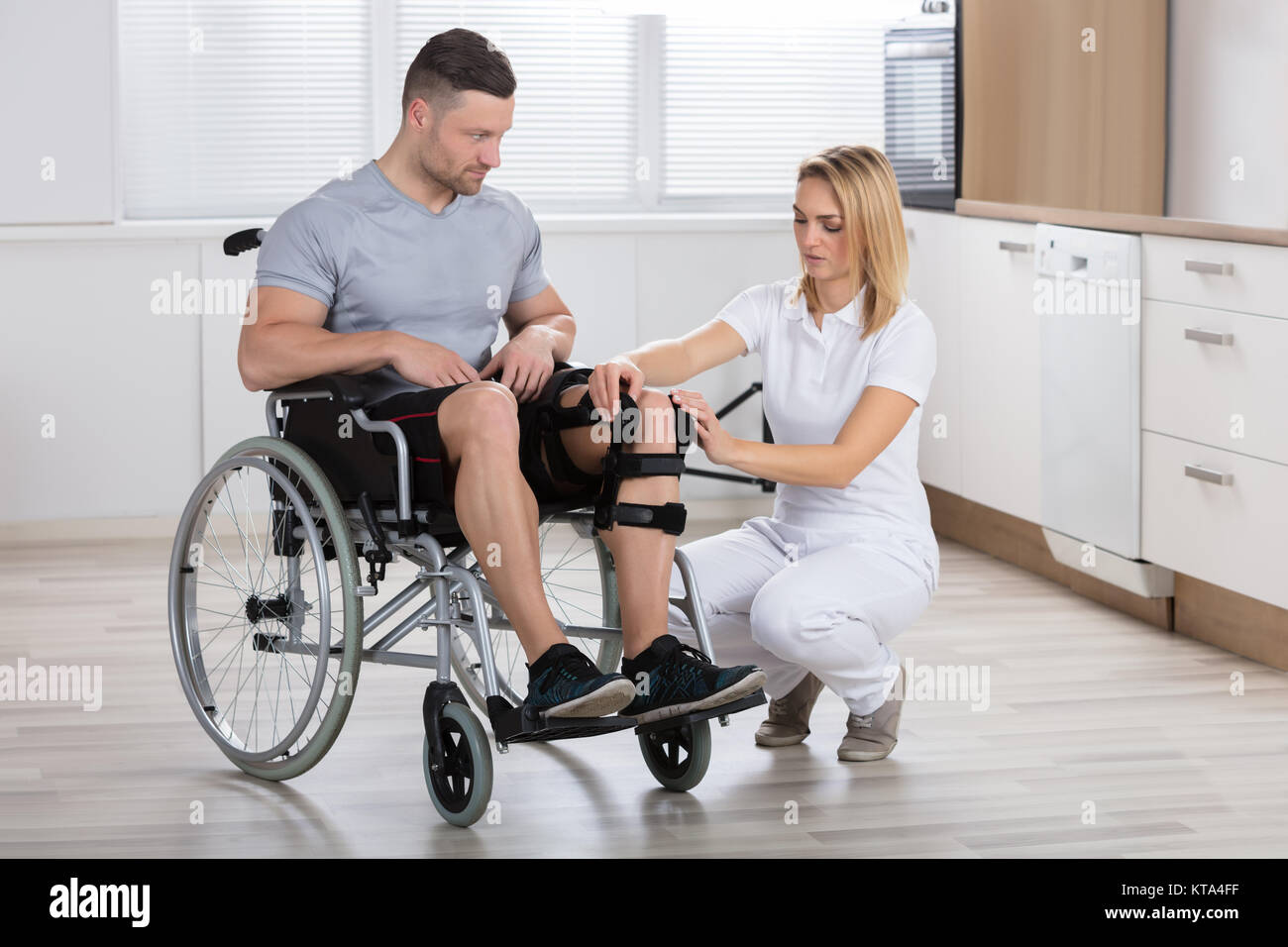 Female Physiotherapist Fixing Knee Braces On Man's Leg - Stock Image
