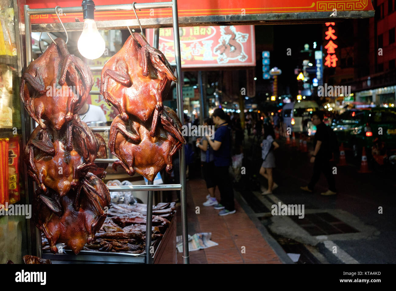 Crispy duck for sale in Bangkok's Chinatown, on the Yaorawat Road. Neon signs and tourists in the background. - Stock Image