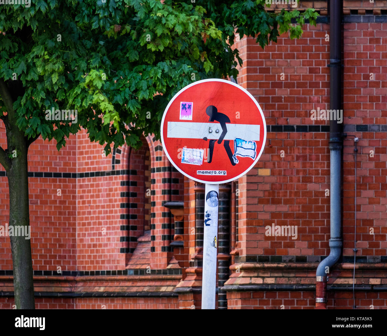 Berlin. Defaced traffic control sign, no entry sign,altered to show man carrying plank,amusing street art - Stock Image