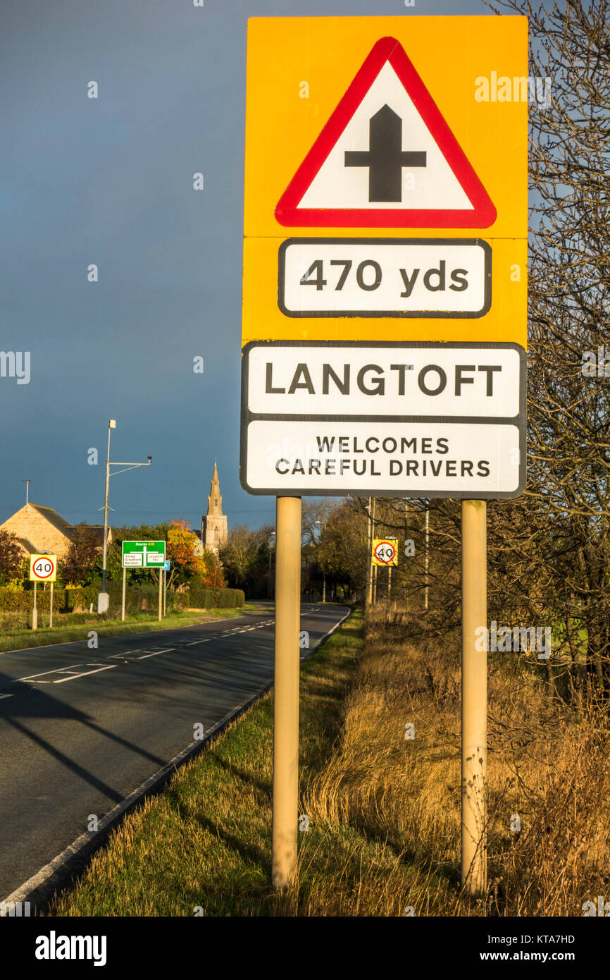 Sunlit 'Langtoft welcomes careful drivers' signpost, positioned just before the village crossroads on the - Stock Image