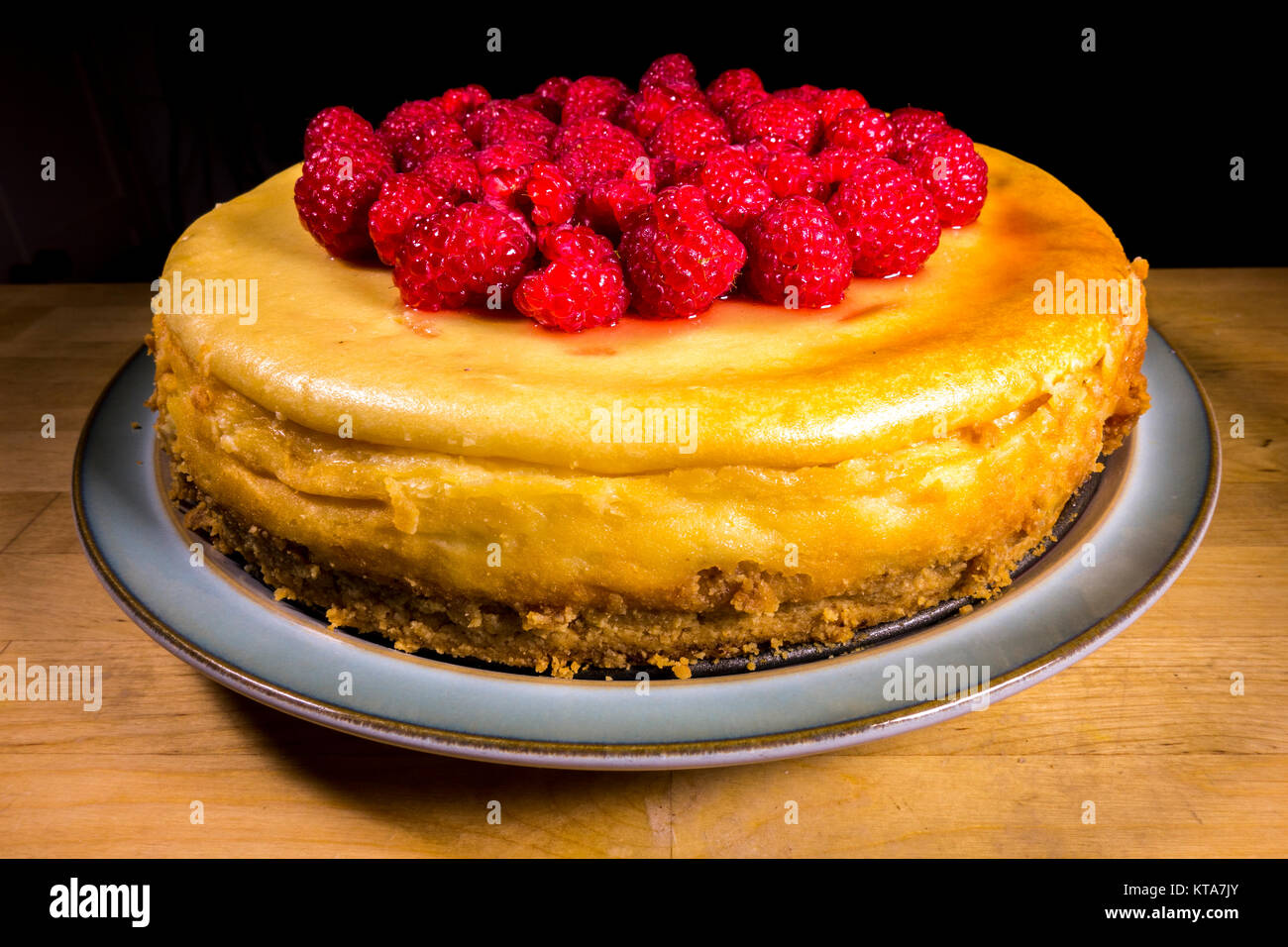 An appetising whole raspberry topped cheesecake sitting on a plate, consisting of a mascarpone cream cheese topping - Stock Image