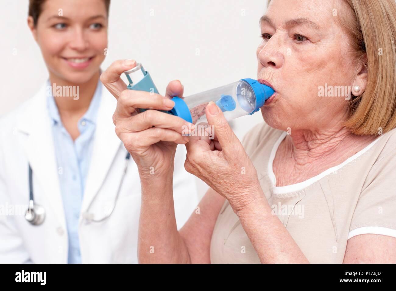 Senior woman using an inhaler, nurse watching. - Stock Image