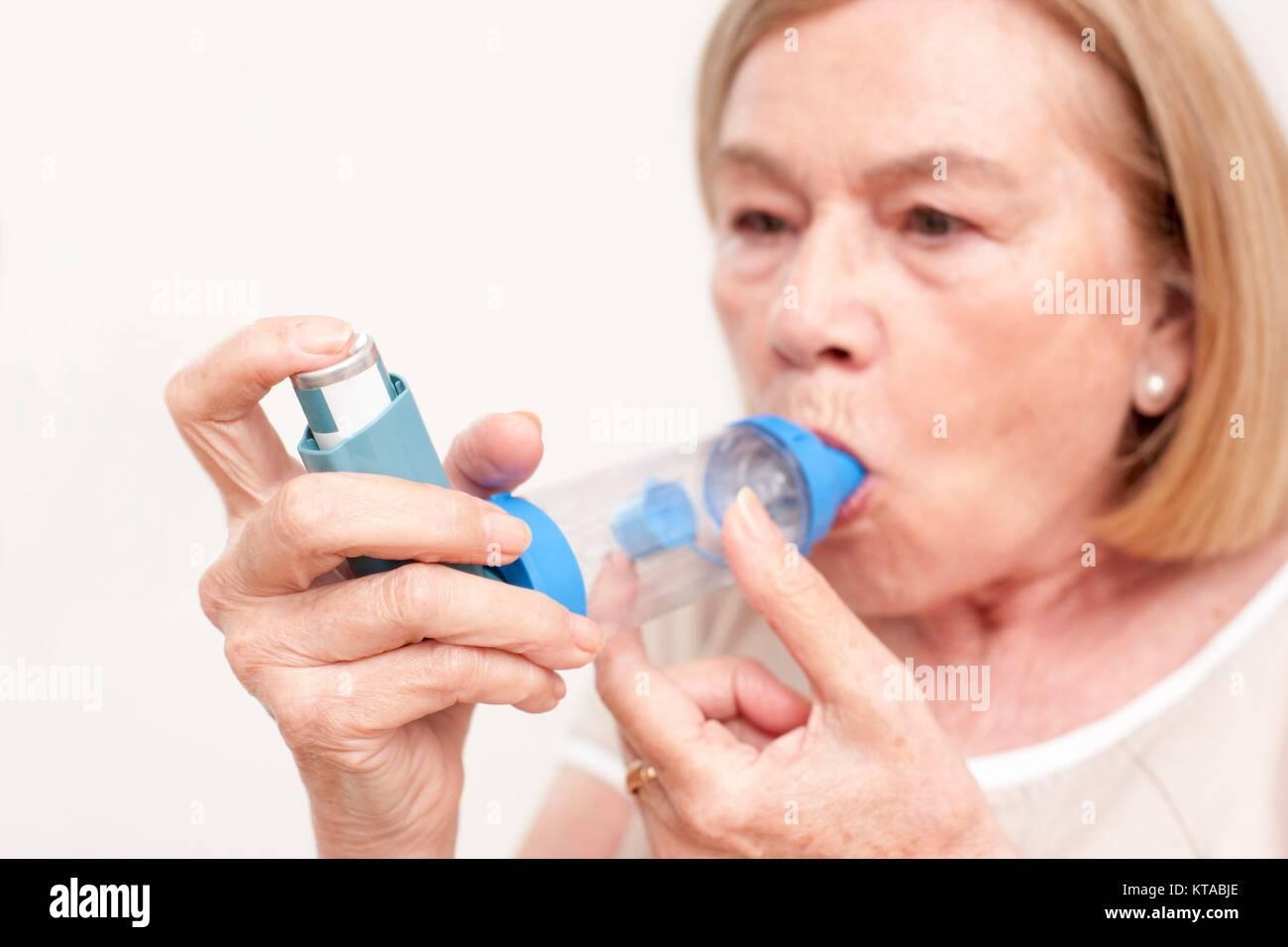 Senior woman using an inhaler. - Stock Image