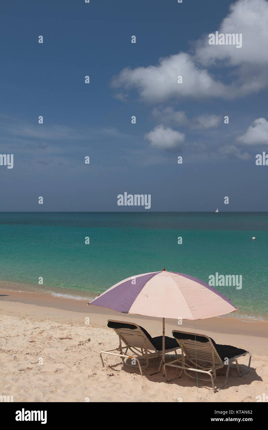 Beach umbrella and chaise lounges on seashore. St. George's, Grenada - Stock Image