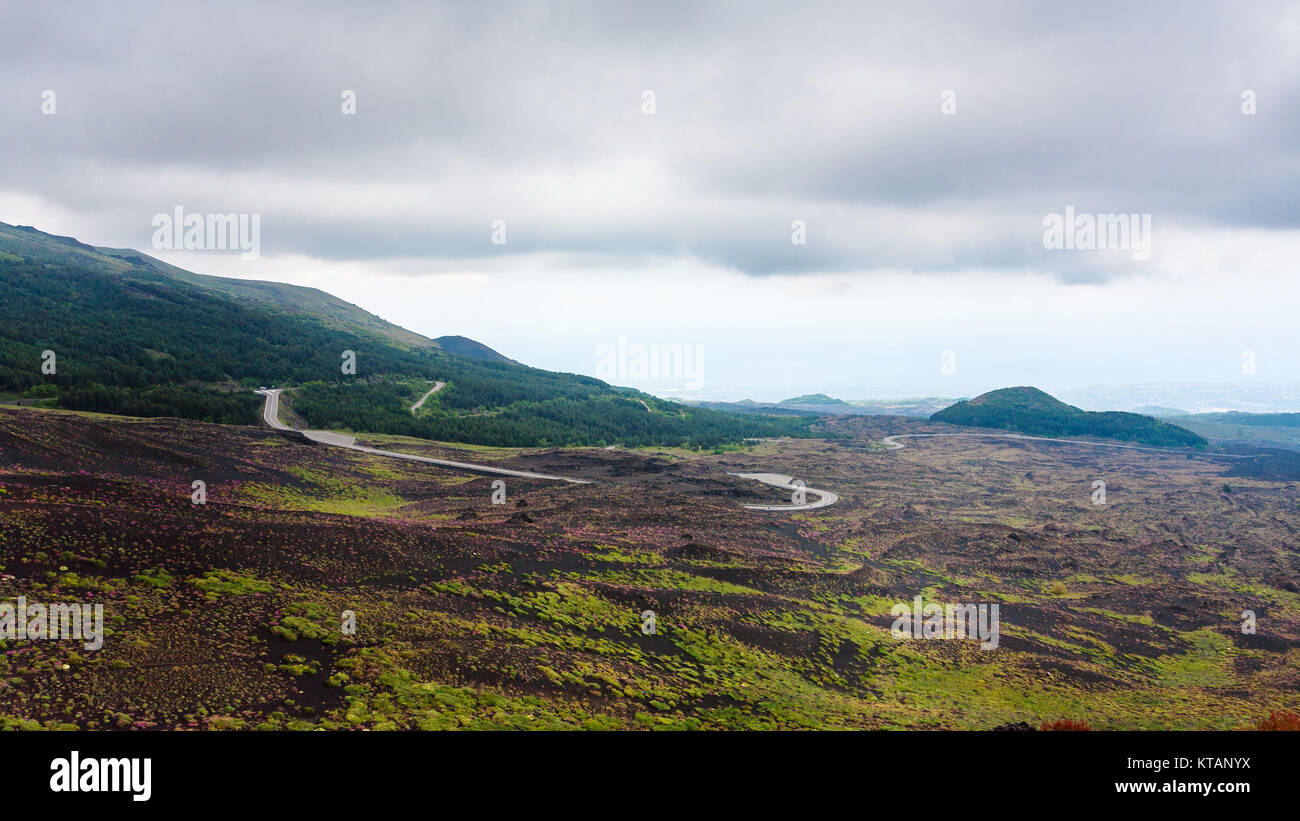 cloudy sky over road in lava fields on Mount Etna - Stock Image
