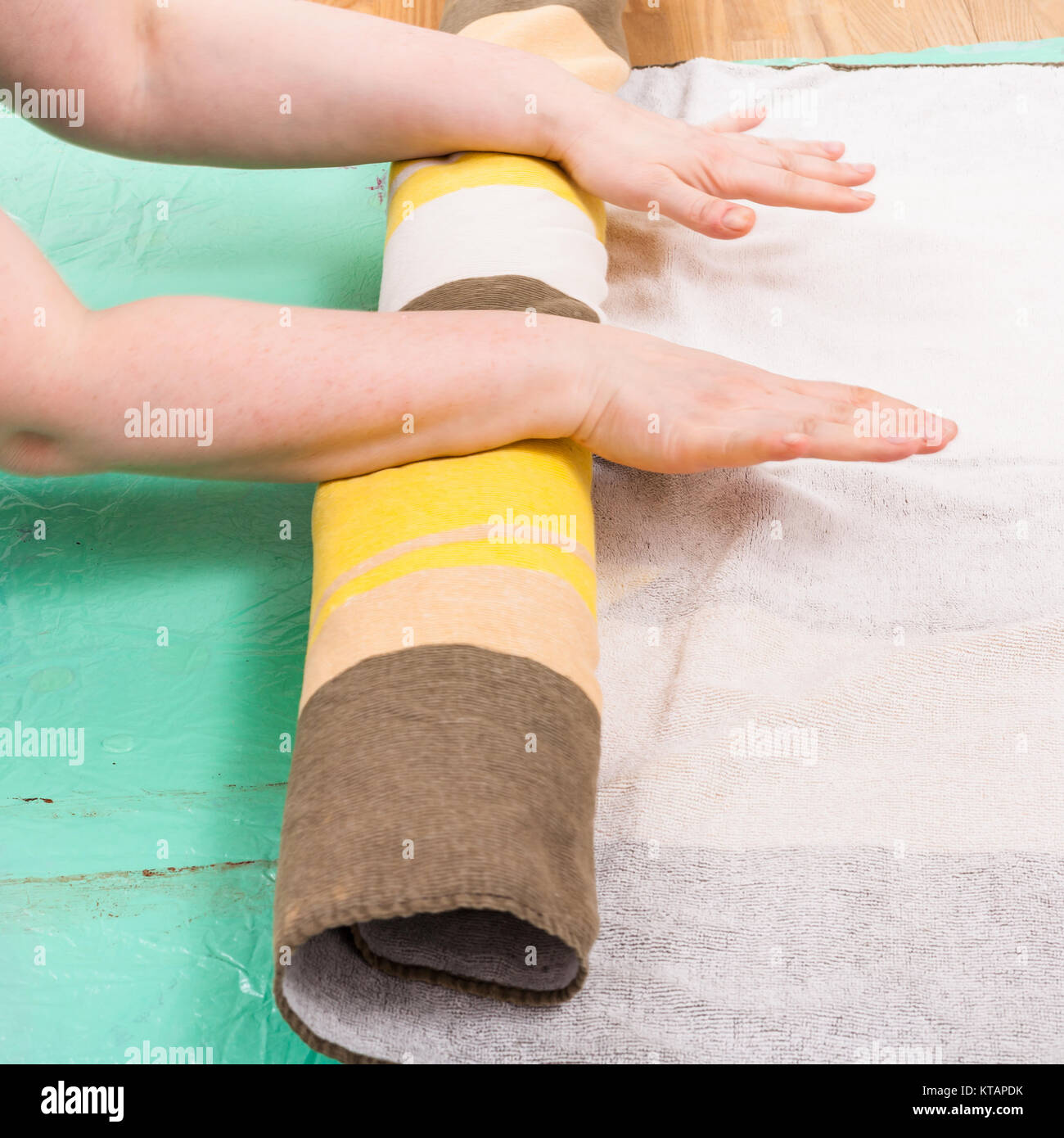 hatter rolls the wool fibers of layout with cloth - Stock Image