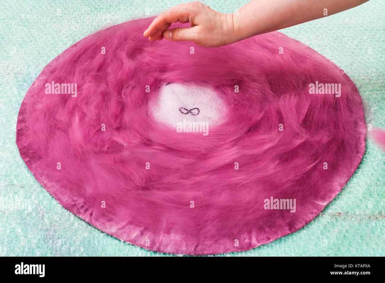 arraging wool fibers on back side of hat layout - Stock Image