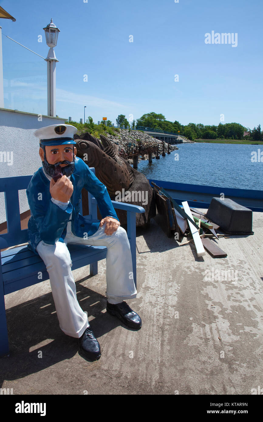 Captain figure on a bench at harbour of Waase, Ummanz island, National park Vorpommersche Boddenlandschaft, Ruegen - Stock Image