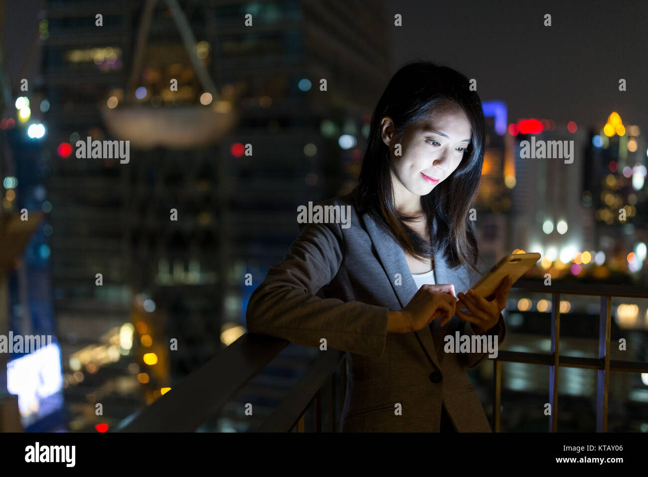 Businesswoman working on cellphone at night - Stock Image