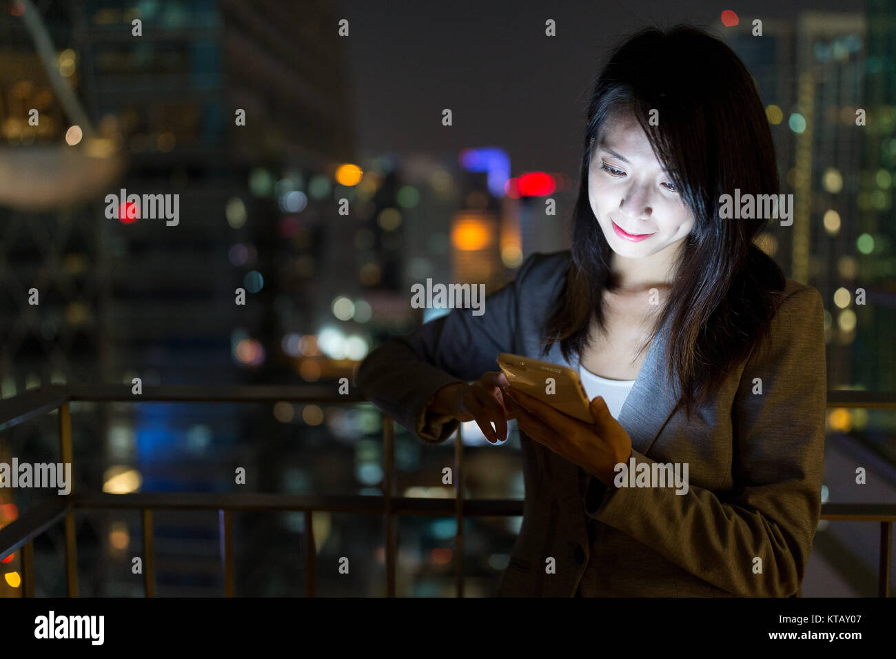 Businesswoman using mobile phone at night - Stock Image