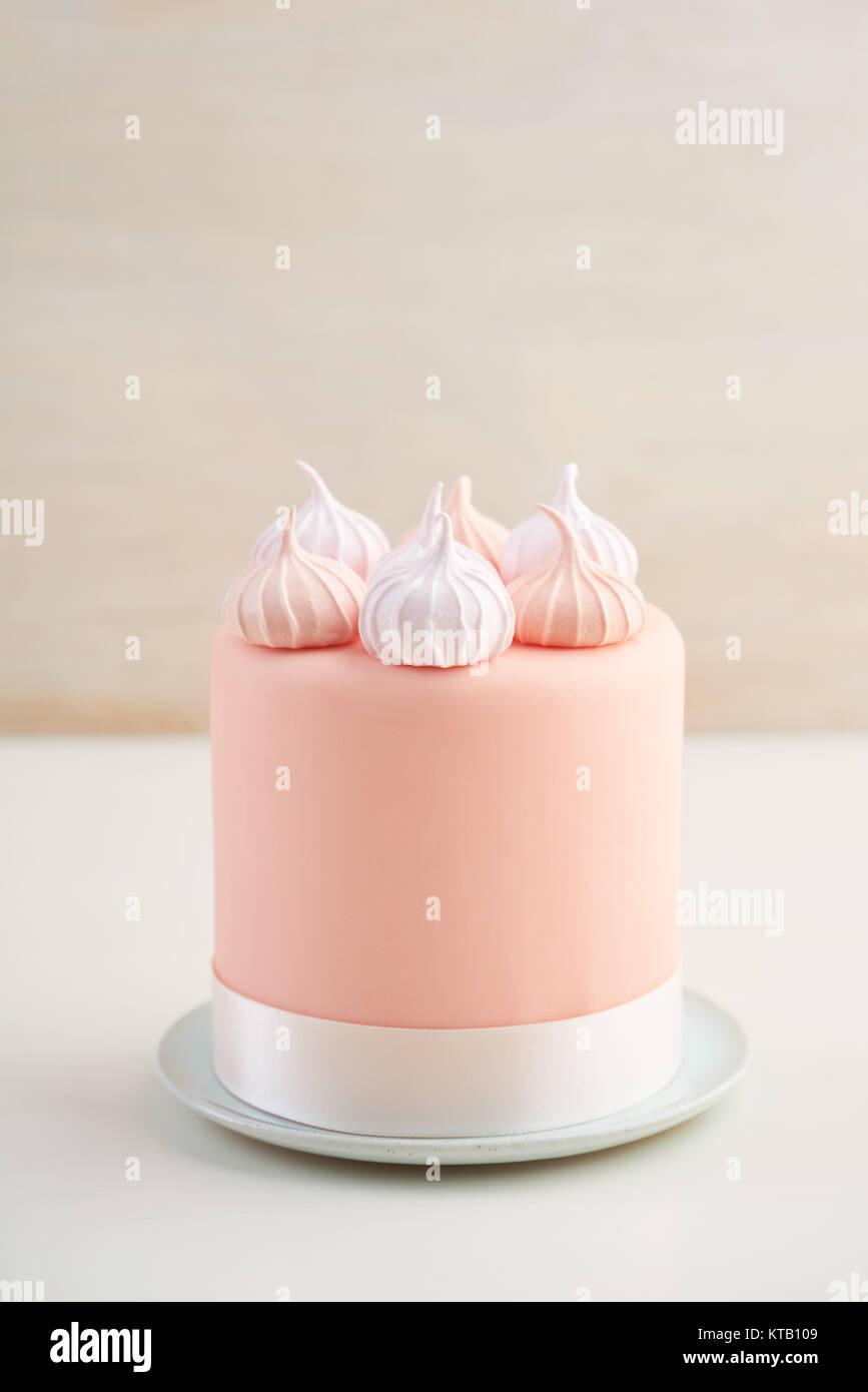 mini fondant covered cake with meringue kisses stock photo