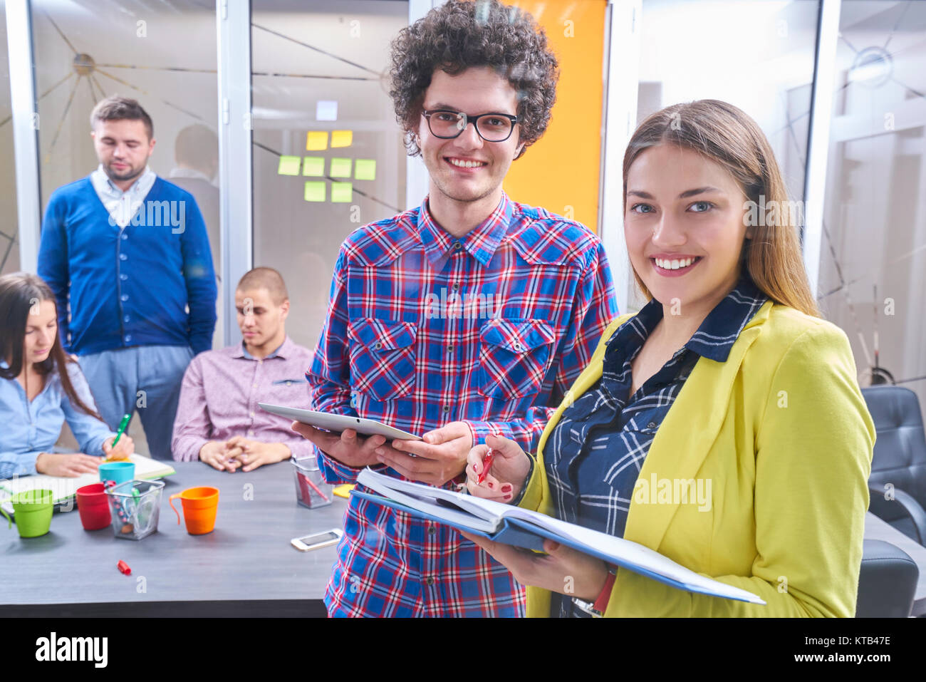 Portrait of startup group of creative people having a meeting with a laptop in a modern office. Business people - Stock Image
