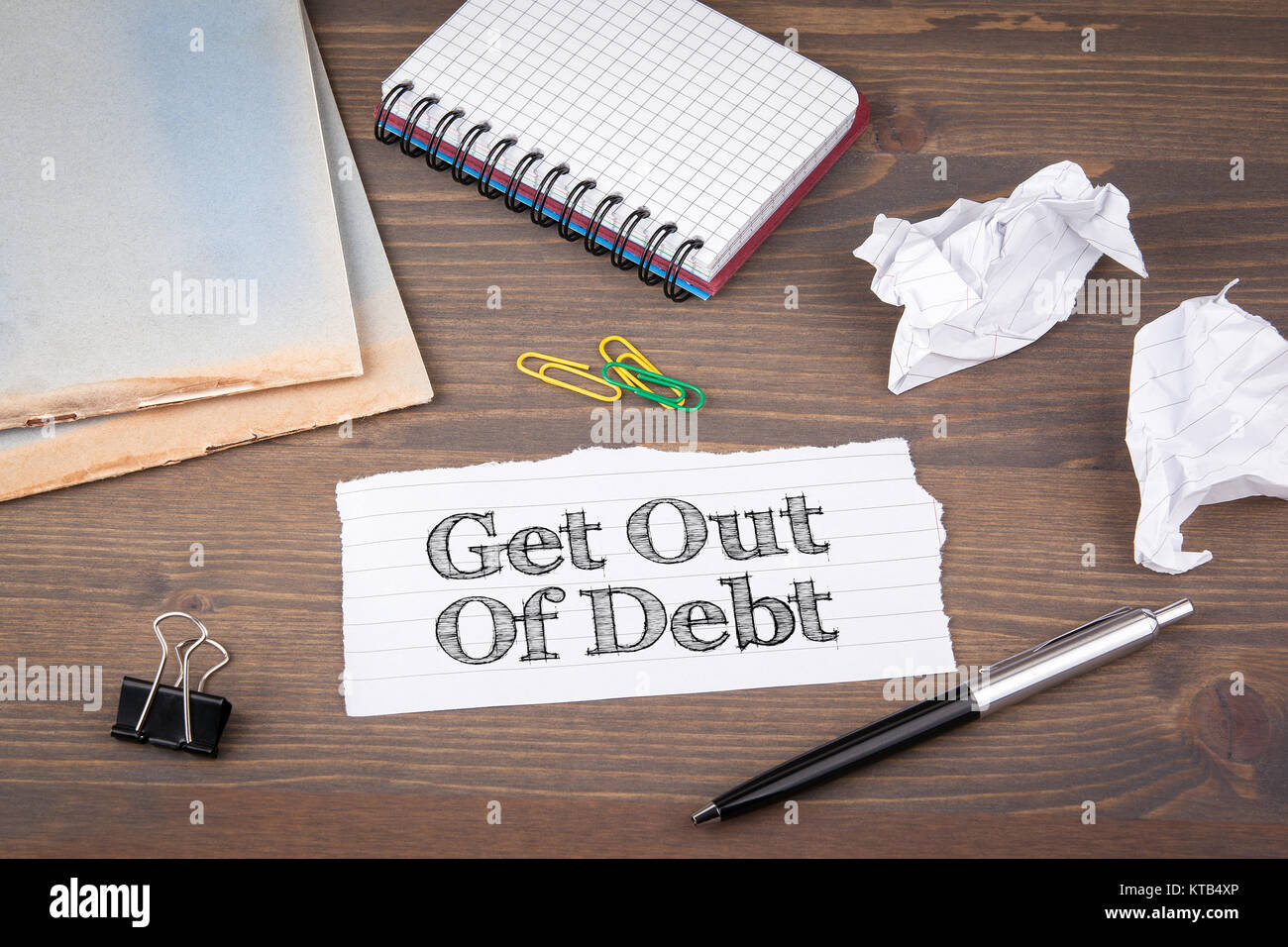 Get Out of Debt. paper sheet from the booklet on the wooden table. - Stock Image
