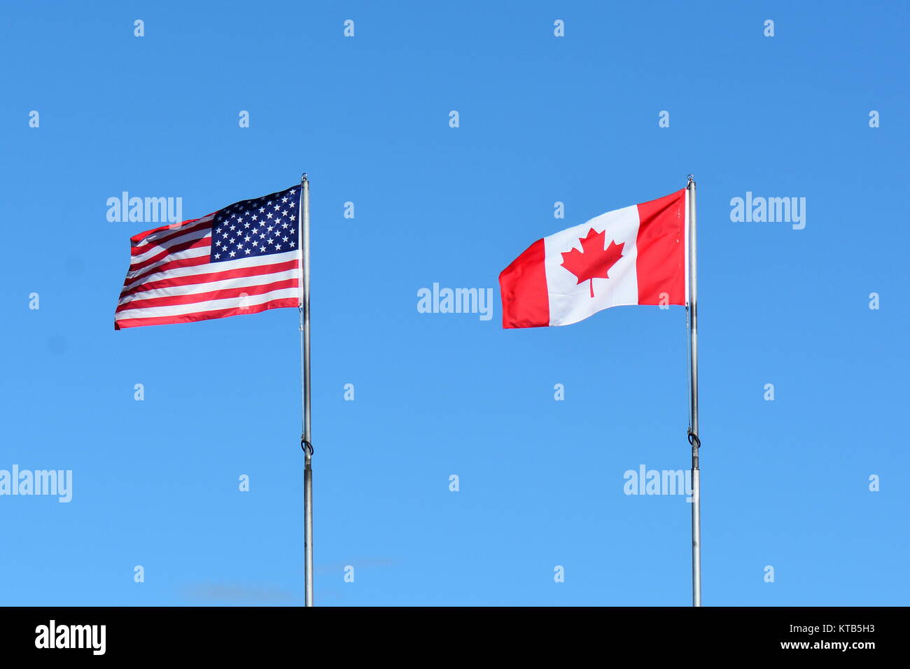 The flags of Canada and the US fly on a flag pole in Victoria BC. - Stock Image