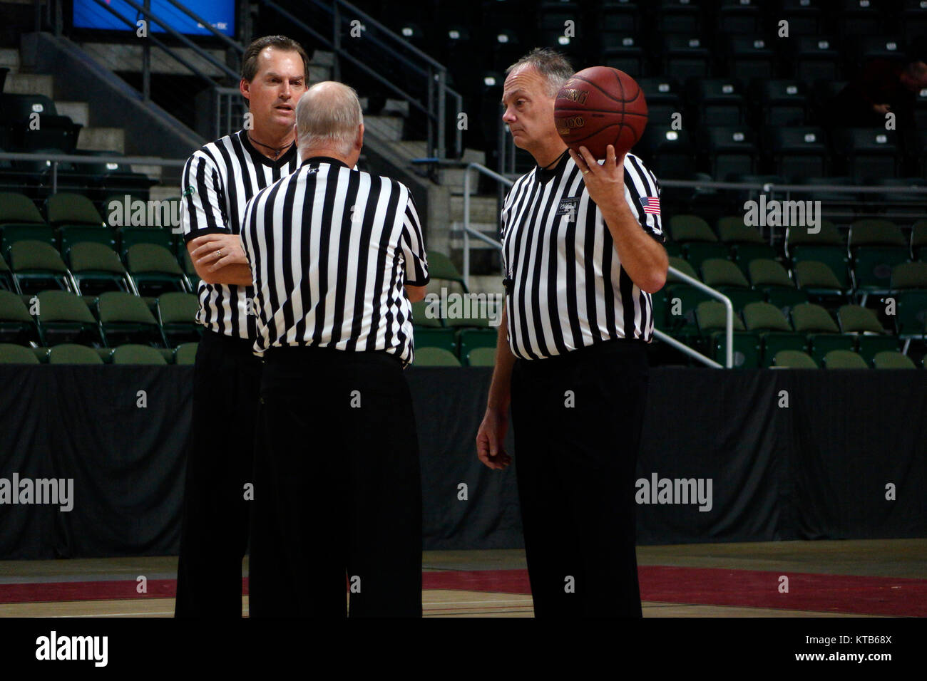 Basketball referees discussing a game during a team timeout. - Stock Image
