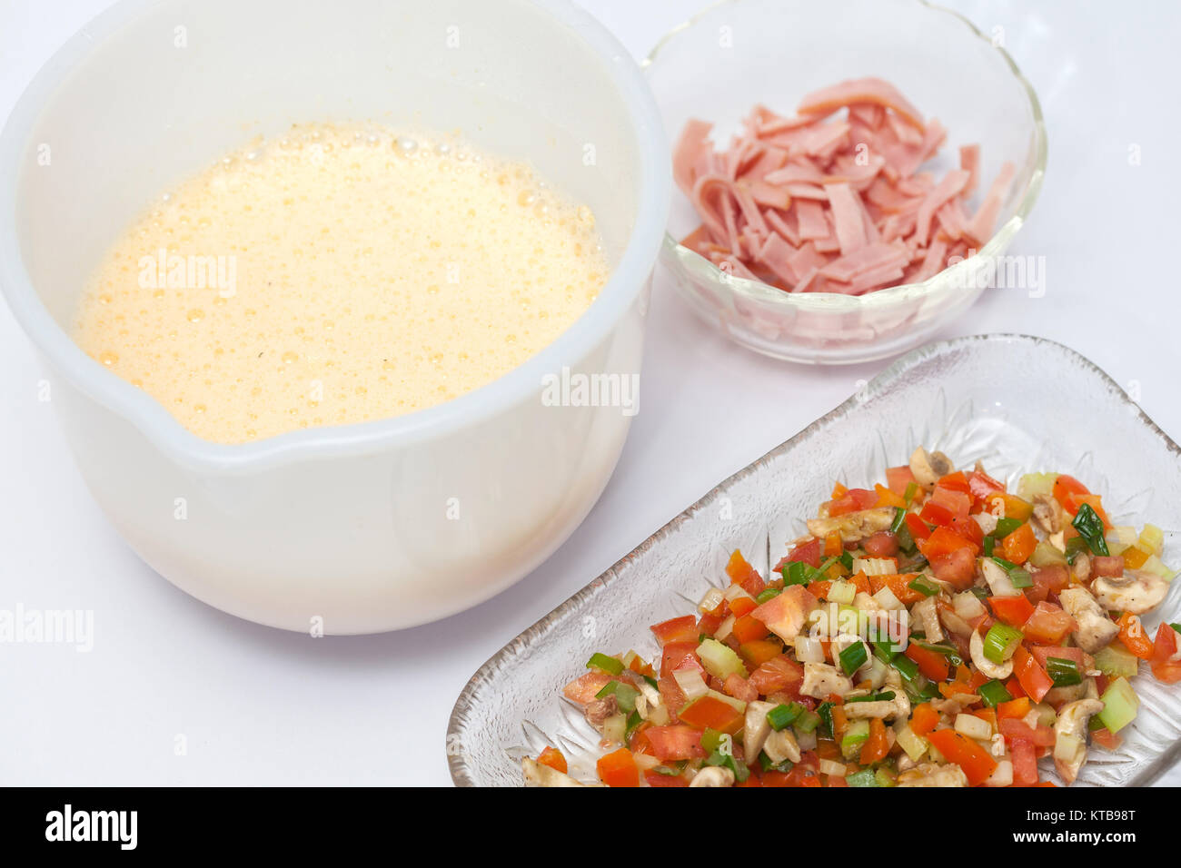 Omelet preparation : Vegetables, ham and scrambled eggs - Stock Image