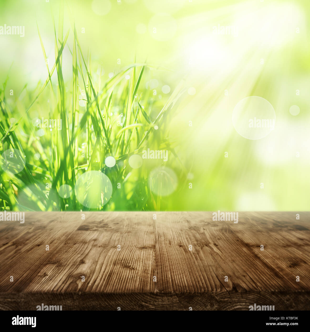 Spring background with green grass in front of an empty rustic wooden table for a concept Stock Photo
