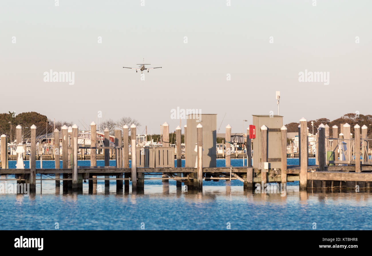 small single engine plane on an approach to montauk's airport, flying over a marina - Stock Image