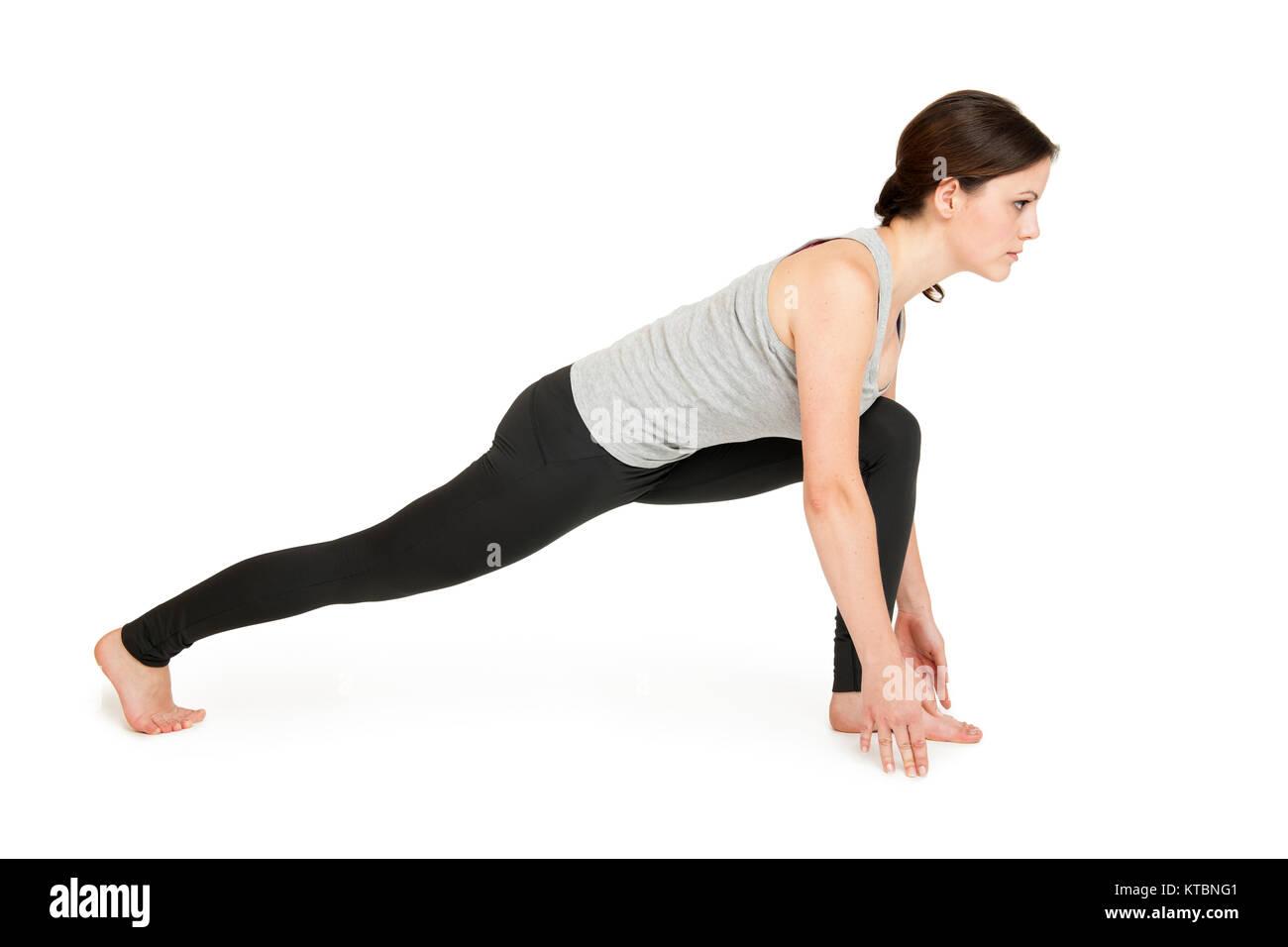 Seitenansicht einer jungen Frau die 4. Position (langer Ausfallschritt) des Yoga-Sonnengrußes zeigend vor weißen Hintergrund Stock Photo