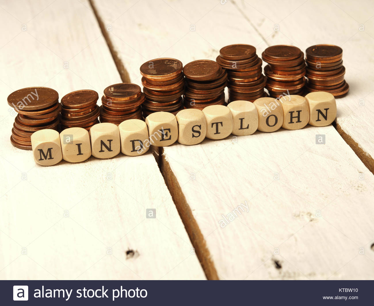 Mindestlohn Konzept mit Holzwürfeln und Kleingeld als Geldstapel - Stock Image
