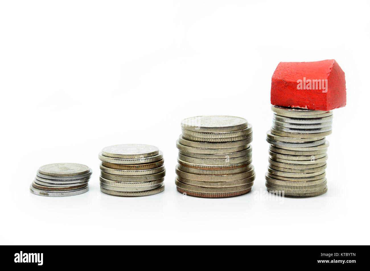 Coins stacked up in piles with color house - Stock Image