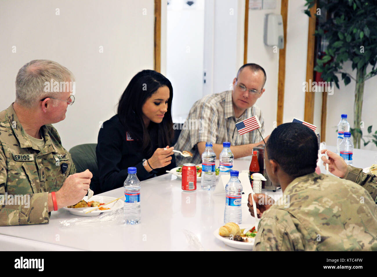Actress Meghan Markle, center, joins military service members for a meal during the USO Holiday troop visit at Bagram - Stock Image