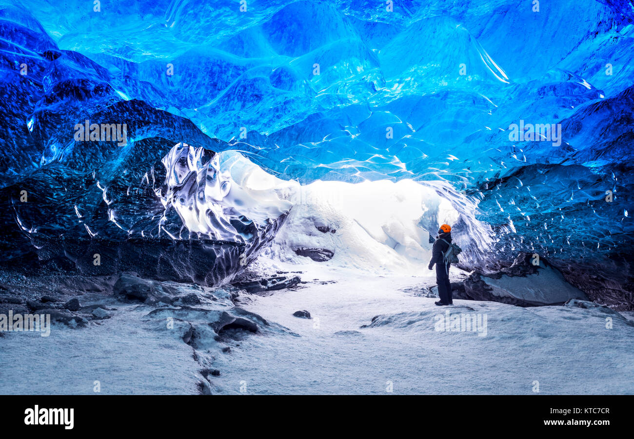 Traveler in ice cave, man standing underground inside of a glacier, climate specific, Vatnajokull National Park, - Stock Image