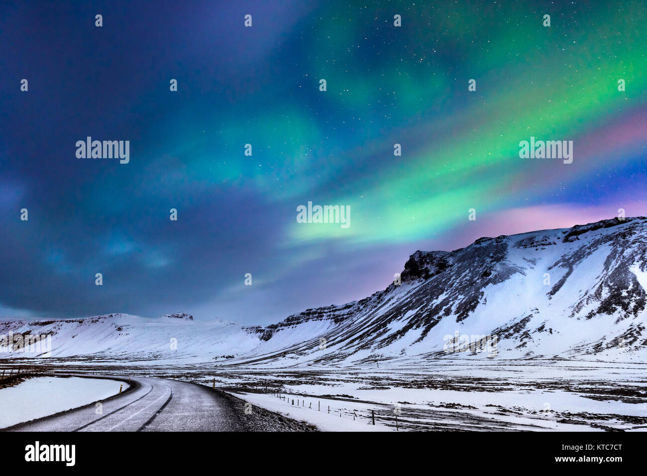 Beautiful landscape of the northern lights over hight mountains covered with snow,  Aurora Borealis, wonderful phenomena - Stock Image