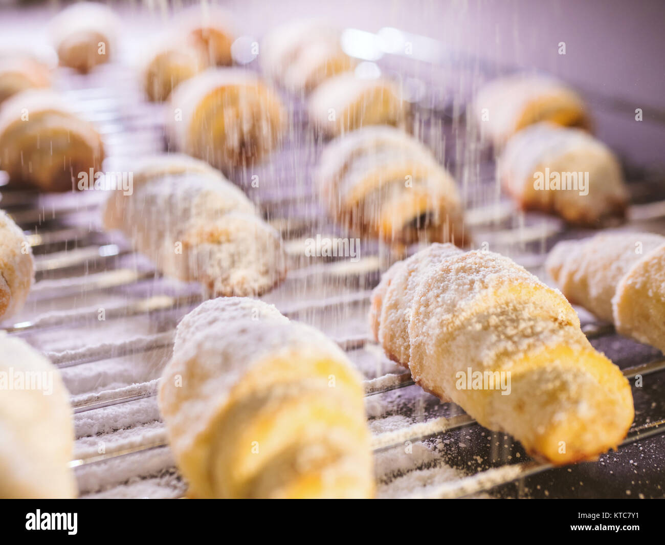 Freshly baked cookies with powdered sugar pouring over them from the sifter. - Stock Image
