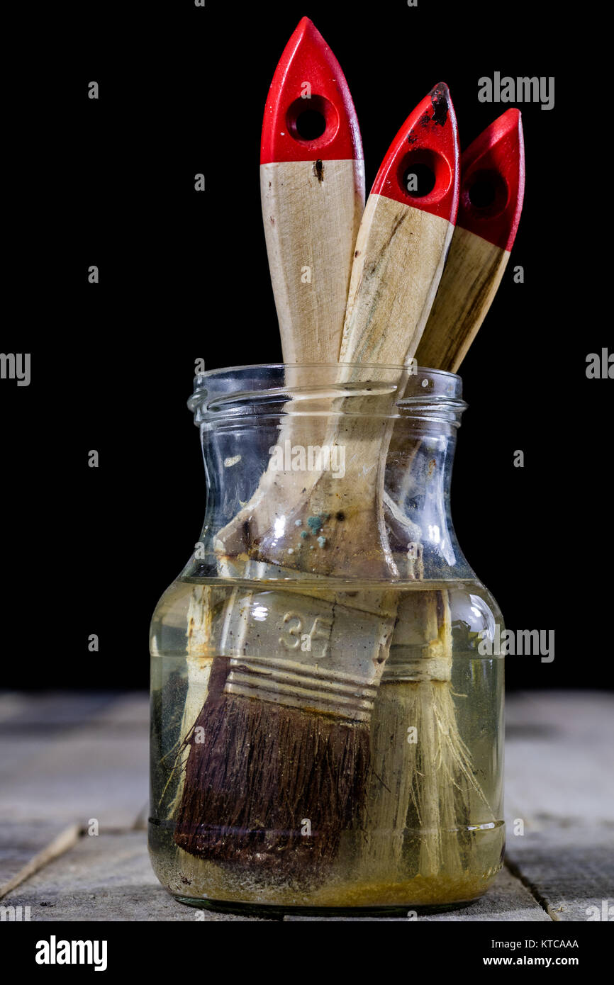 Painting pedzels soaked in water on a wooden workshop table. Painting accessories. Black background. - Stock Image