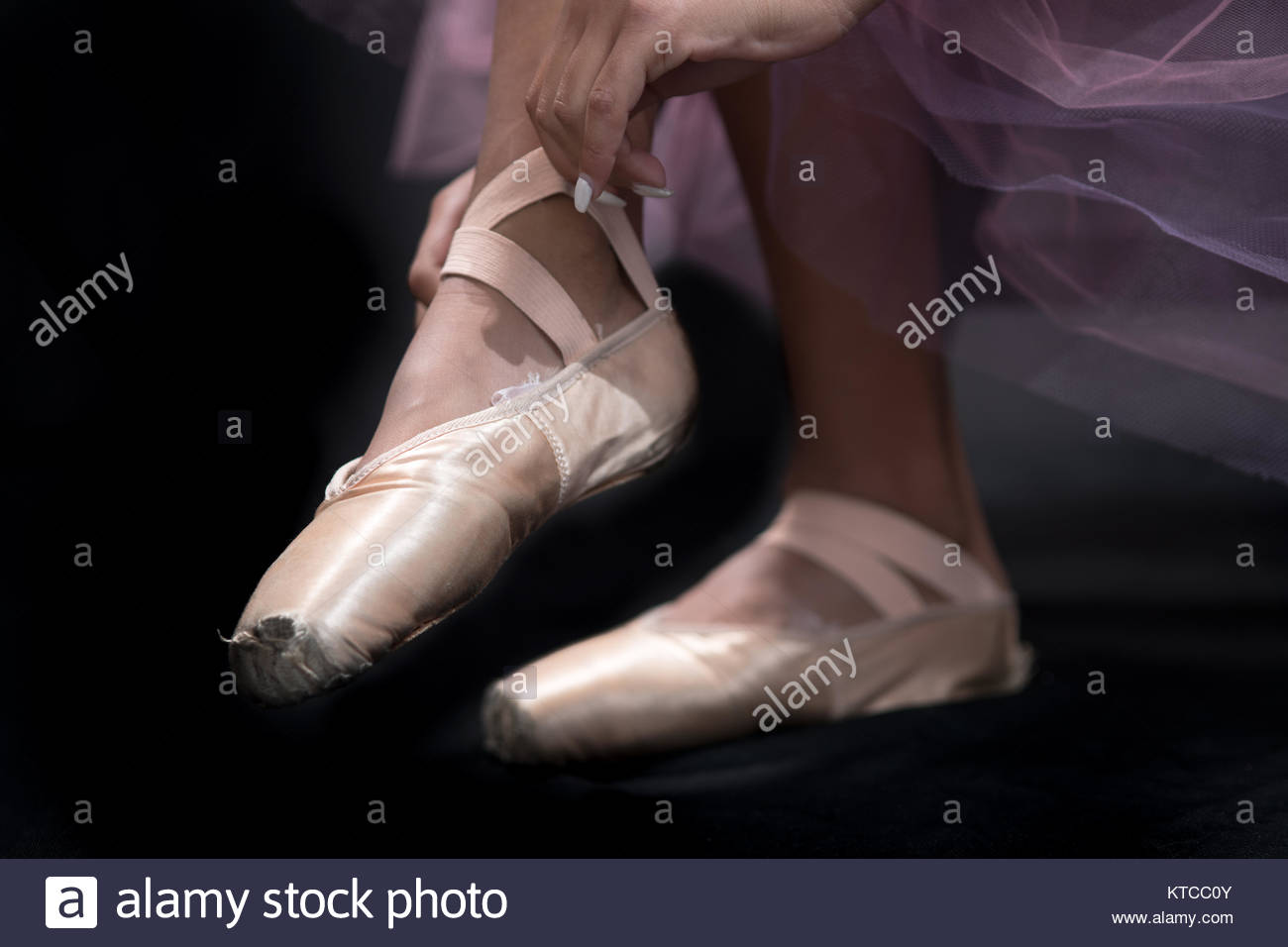 feet of a teen girl ballerina in points, adjusting shoes. - Stock Image