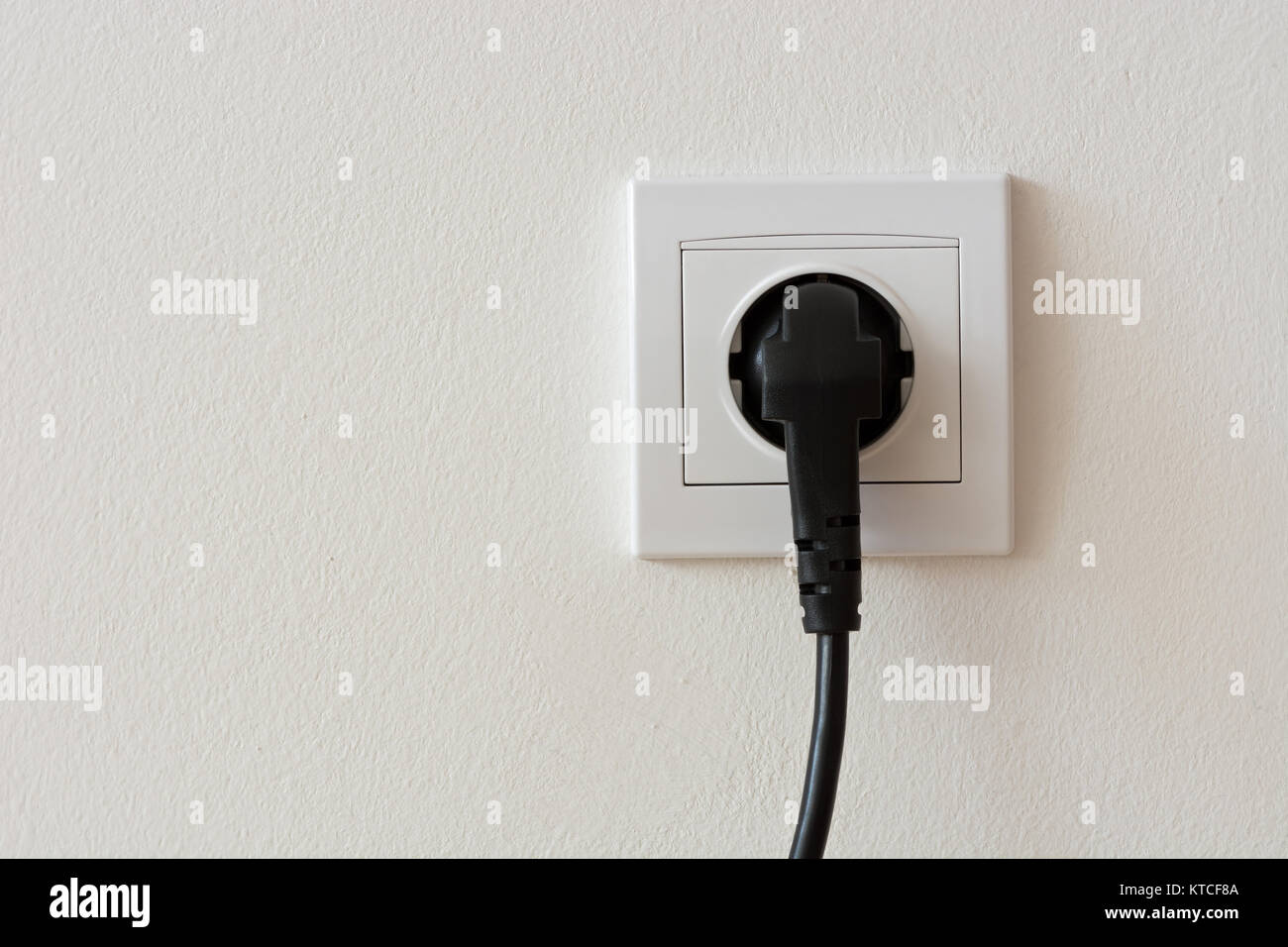 Close up photo of a black 220 volt power plug plugged in a socket ...