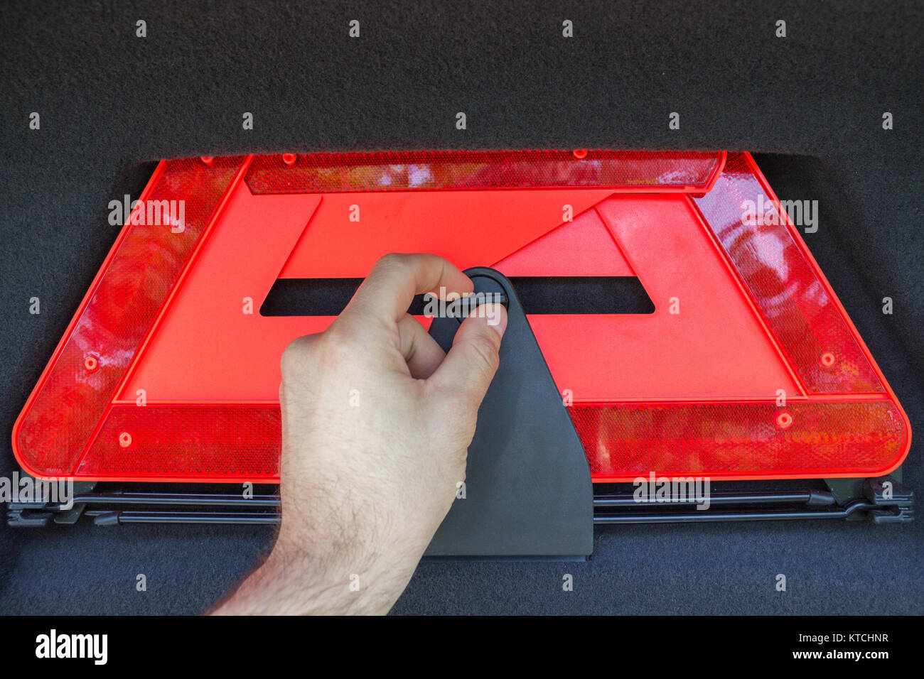 A man hand pulls out a red folded emergency sign lies from the trunk. - Stock Image