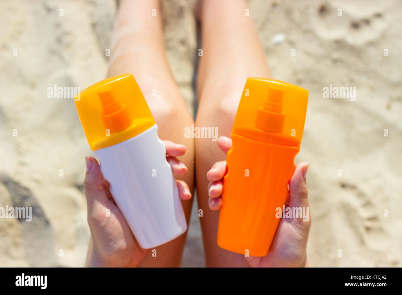 A woman holding two bottles of sunscreen in her hands. A girl chooses between two bottles of sunscreen - Stock Image