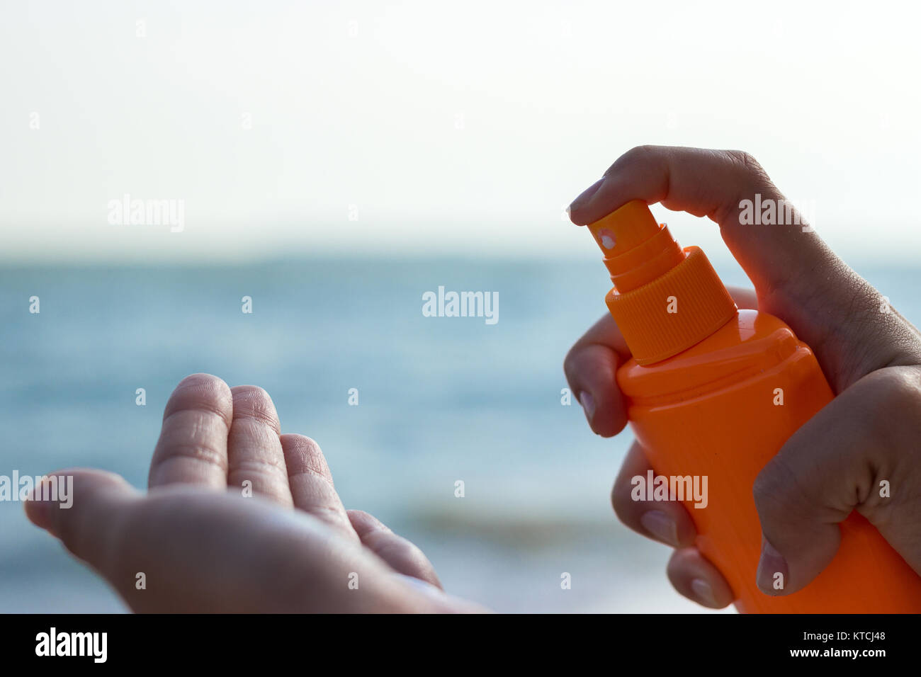 Woman pouring sun protection cream in a hand - Stock Image